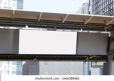 Blank horizontal billboard hanging on metal beam on urban train transports  outdoor station with city building on background .