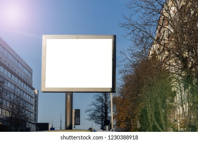 blank horizontal billboard on road with city view background and lens flare for advertising