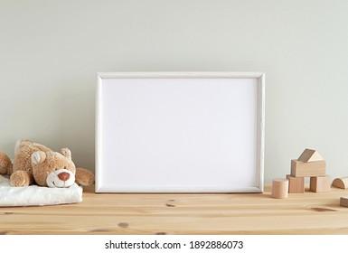 Blank horizontal frame mockup, nursery framed wall art, baby room art, empty frame for print, photo, wooden shelf, baby toys and blanket.   - Shutterstock ID 1892886073