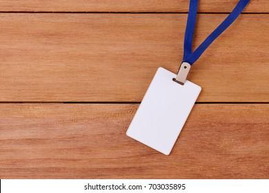 Leere Identifizierungskarte mit Neckband auf Holzhintergrund. Draufsicht der Badge-ID oder Name-Tag.