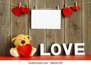 Blank instant photo hanging on rope with lovely hearts, cute teddy bear with the word love on rustic wooden wall.