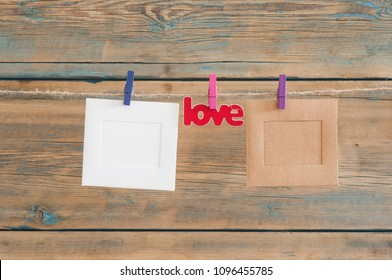 blank instant photos hanging on the clothesline with word love on wooden background