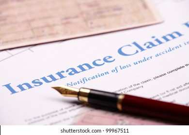 Blank insurance claim form and other papers like ID or vehicle documents and pen lying on desk