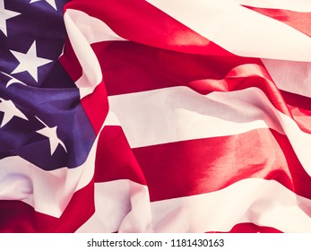 Blank invitation card for Your inscriptions on a background of the waving flag of the USA. Top view, close-up. Preparing for the holidays