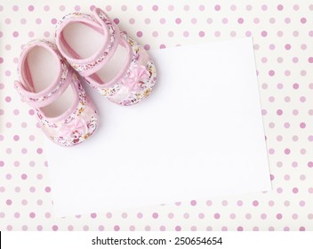 Blank invitations card with pink floral baby girl shoes on a pastel pink spotted background.