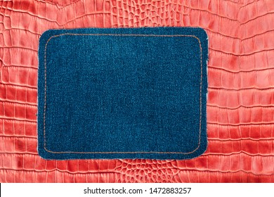 Blank jeans frame. Denim patch with orange thread seam on red skin. With space for design, text place.