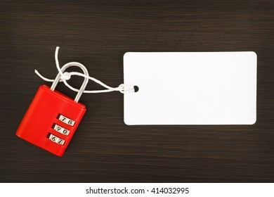 Blank label tag with combination number padlock on wooden background
