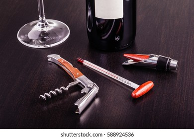 a blank labeled bottle of wine and a glass of wine and some wine tools on a dark wooden surface