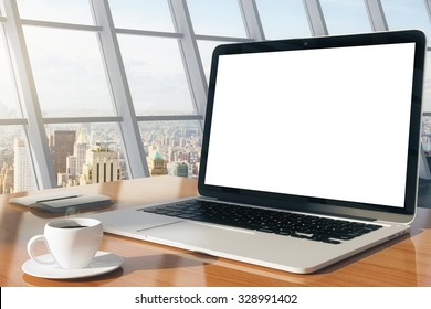Blank laptop on a wooden table in a modern office with cup of coffee, mock up