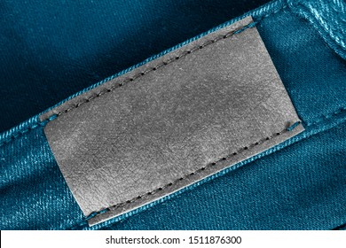 Blank leather clothes label on blue denim background