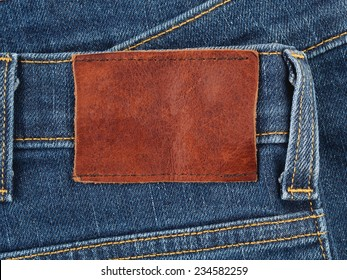 Blank leather label on a blue denim jeans, fabric background with copy space