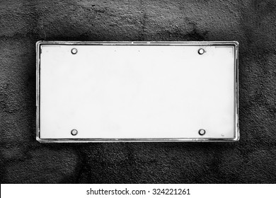 blank license plate on dark crack wall background  ,black and white tone