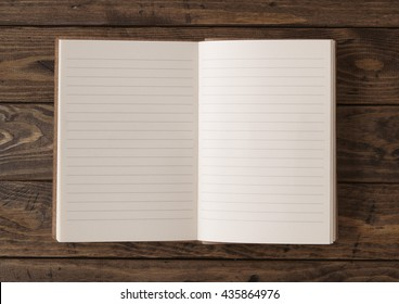 A blank, lined writers journal laid open on a wooden desk top background
