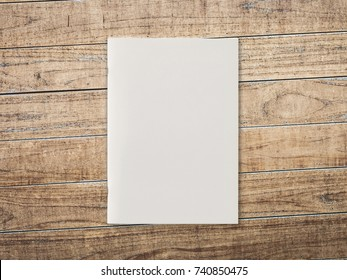 Blank Magazine or Brochure on brown wooden background. Front cover top view. Mockup concept for your showcase.