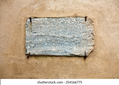 Blank marble signboard close-up over wall hold by four rusty nails