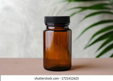 Blank medical bottle mockup for pills. Transparent dark bottle of amber glass with green plant. Herbal medicine concept.