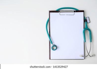 Leere medizinische Zwischenablage mit Stethoskop auf weißem Hintergrund. Kopiert Platz.