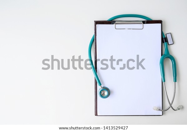 Blank medical clipboard with stethoscope on white background. Copy space.