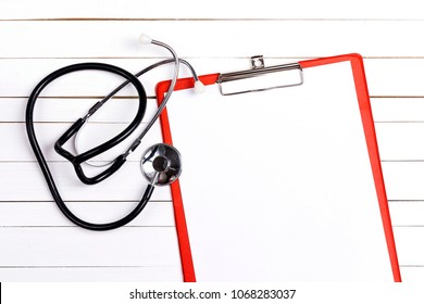 Blank medical folder with the stethoscope on white desktop. Top view, copy spase for text.
