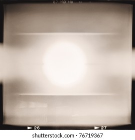 Blank medium format (6x6) monochrome film frame with abstract filling containing light leak in center, grain effect added