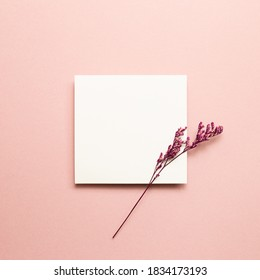Blank memo pad, empty paper with misty blue dry flower on pink background. top view, copy space