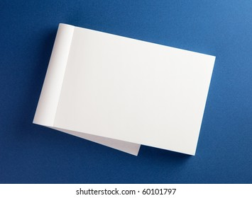 Blank memo pad with page folded back on blue surface.