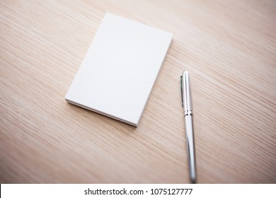 A blank memo pad and a silver pen, on a light colored wood table.