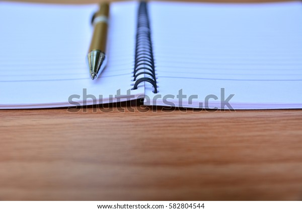 Blank memory book with pen on wooden table.