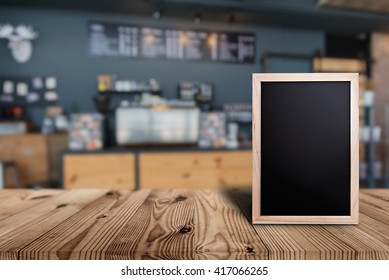 Blank menu board on wooden top table with blurred of coffee shop background