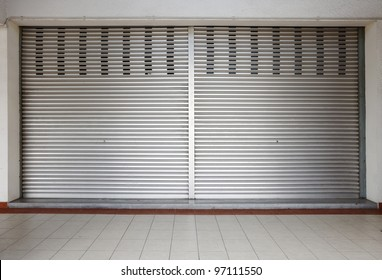 A blank metal shutter door, with space for text, on a modern urban commercial shop front.