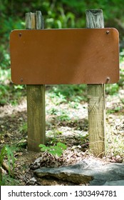 Blank metal sign on wood posts against forest background.