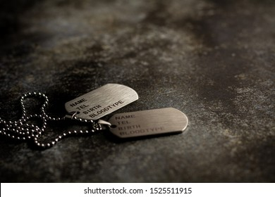 Blank military dog tags on abandoned rusty metal plate. - Memories and sacrifices concept.