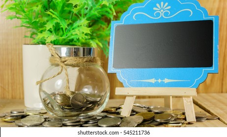 Blank mini chalkboard and coin in the jar with blurred background of green plant. Financial Concept.
