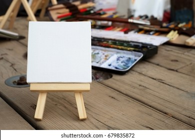 Blank Miniature Canvas on a wooden crate with art supplies at the background. Horizontal shot.
