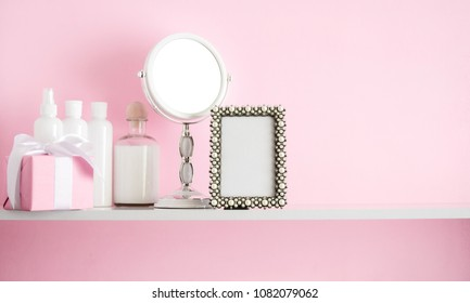 Blank mock up of photo frame on the pink background. Cosmetic set on light dressing table.Beautiful flowers in a vase on a pink wall background, gift, mirror on a wooden shelf.
