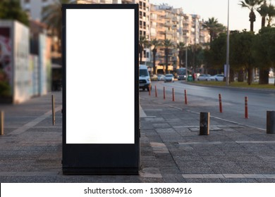 Blank mock up of vertical street poster billboard on street with traffic at night.