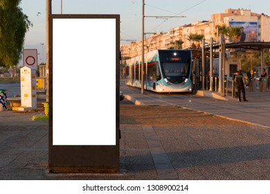 Blank mock up of vertical street poster billboard on tram stop background with station passengers.