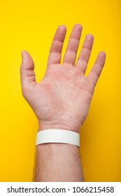 Blank mockup bracelet on hand, isolated on yellow background. Concert paper wristband.