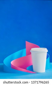 Blank mock-up paper cup in pastel colors with a modern paper craft sculpture on a vibrant background. Creative design for HoReCa.