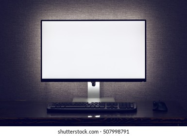 Blank monitor with keyboard and mouse with backlight over gray wall in dark room