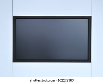 blank monitor screen hanged on white wall