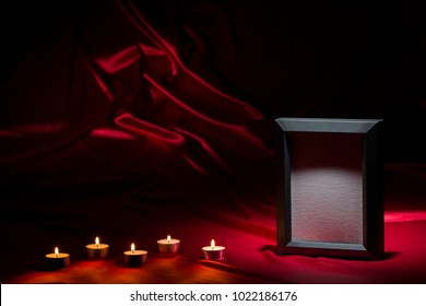 Blank mourning frame with candles on red background