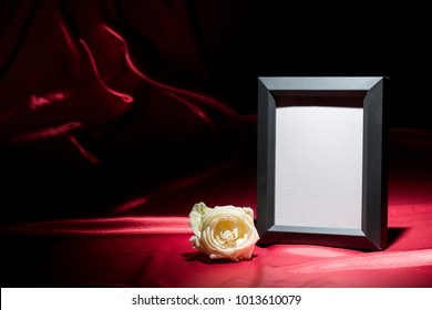 Blank mourning frame on deep red perianth with white rose