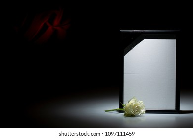 Blank mourning frame with smoky candle on dark background with red decoration