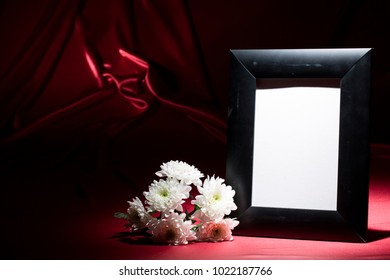 Blank mourning frame with white chrysanthemum on deep red perianth
