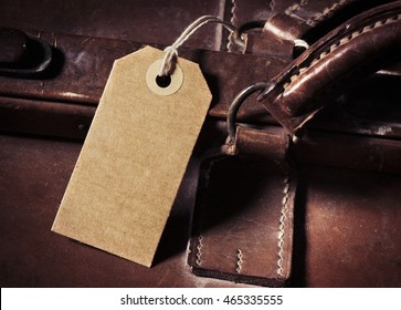 Blank name tag with copy space on old vintage suitcase. Concept of travel with luggage, tourism and holiday destination.