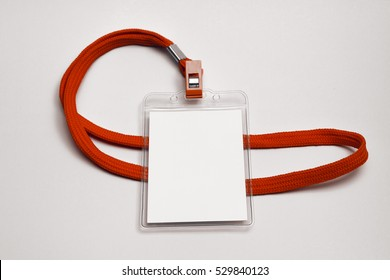 Blank name tag in a plastic sleeve, with red lanyard. Name tag is blank for your text.