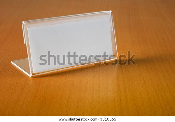 Blank nameplate on beech wood desk, reflecting slightly.