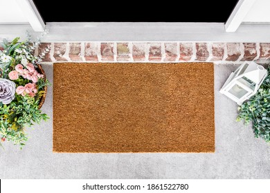 Blank natural door mat in front of entrance door with flowes, doormat mockup