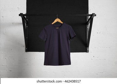 Blank navy athletic cotton t-shirt presented on wooden hang on pullbar ahead of brick wall